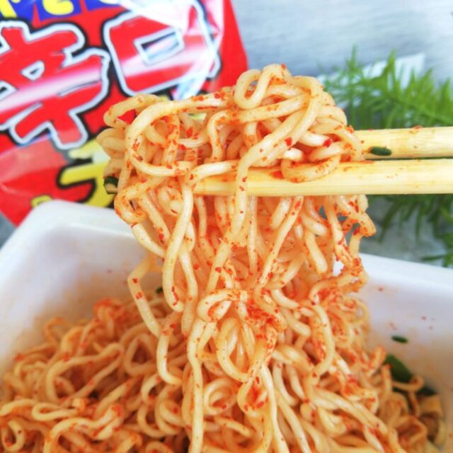 ペヤング辛口チゲの麺を箸で持ち上げる