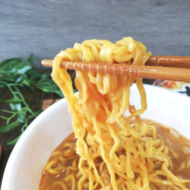 セブンイレブン「すみれ」のカップラーメンの麺を箸で持ち上げているところ
